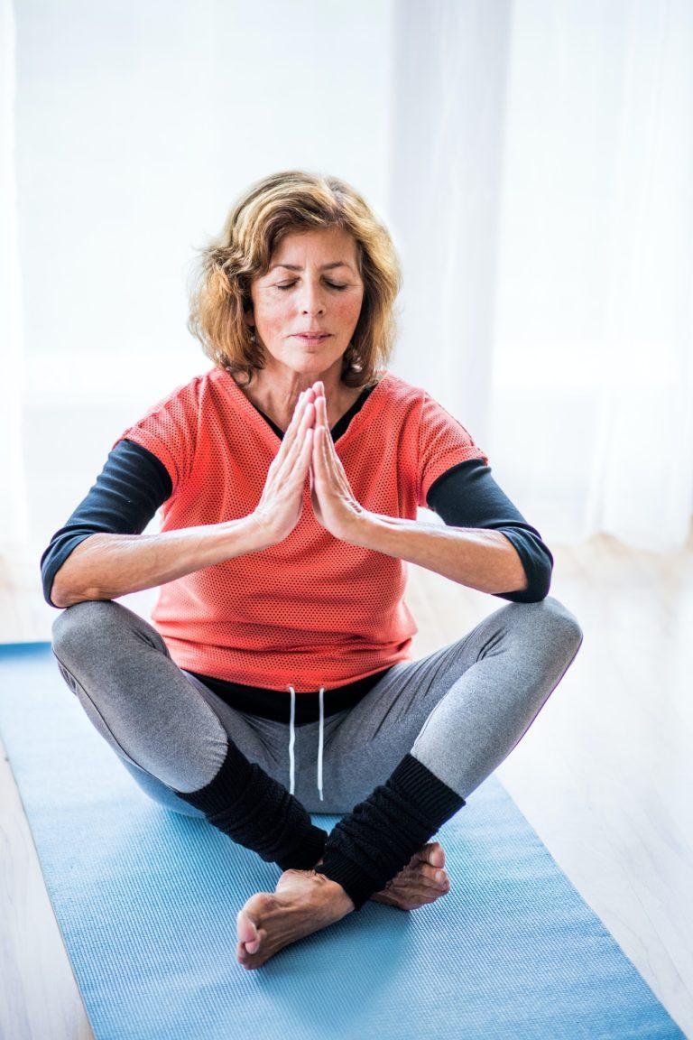 A contented senior woman meditating at home.