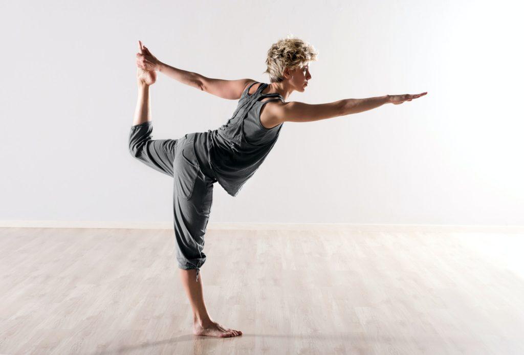 Young woman doing yoga balancing exercises